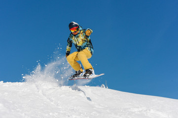 Young active snowboarder in bright sportswear jumping up on a mountain slope