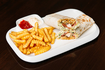 Shawarma sandwich gyro- fresh roll of thin lavash (pita bread) filled with grilled meat, mushrooms, cheese, cabbage, carrots, sauce, green. Traditional Eastern snack. On a wooden background