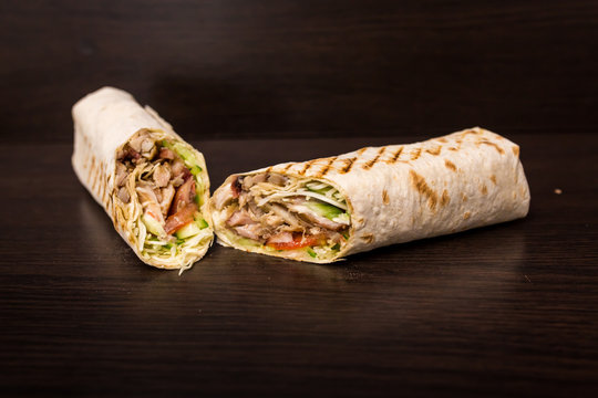 Shawarma sandwich - fresh roll of thin lavash (pita bread) filled with grilled meat, mushrooms, cheese, cabbage, carrots, sauce, green. Traditional Eastern snack. On a wooden background