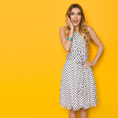 Surprised Young Woman In Summer Dress Is Holding Hand On Chin