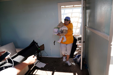 A woman carries a teddy bear out of her friend's destroyed house following Hurricane Michael in Mexico Beach