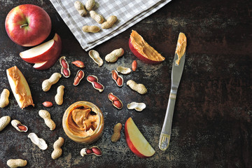 Jar of peanut butter, peanuts in a peel, apple slices and a knife. Peanut butter apples on a stylish authentic table.
