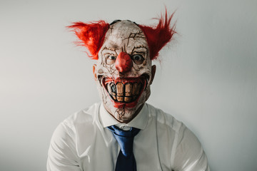 Closeup of a scary evil clown prepared for halloween, wearing a white shirt and blue tie. Thematic photos.