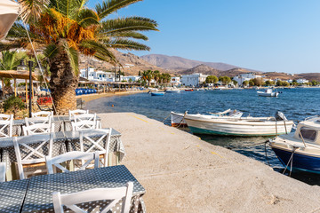 Tables with chairs on coastal promenade in Livadi. Serifos island, Greece