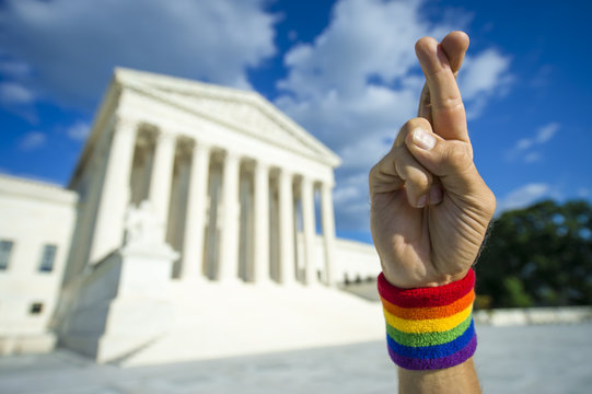 Hopeful hand wearing gay pride rainbow flag wristband crossing fingers for good luck outside the Supreme Court building in Washington, DC, USA