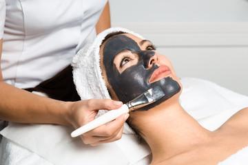 Fototapeta Beautiful woman receiving clay facial mask with rejuvenating effects in spa beauty salon. obraz