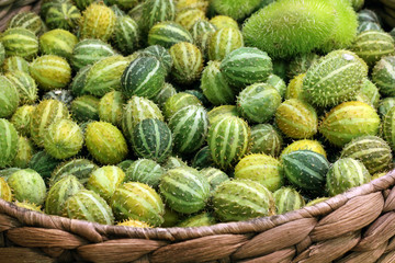 small decorative cucumbers in a wicker basket