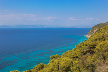 A view over the pine forest on the turquoise sea. Fantastic view of the west coast of Lefkada island, Greece, Europe. Beauty of nature concept background.