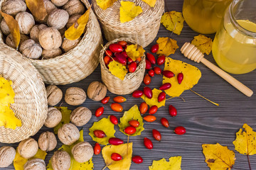 Walnuts, honey, rose hips and yellow leaves on a wooden surface, healthy food from nature. Concept of autumn background