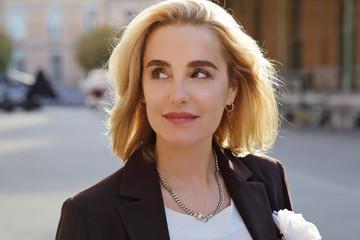 jolie femme blonde élégante au soleil d'automne souriant