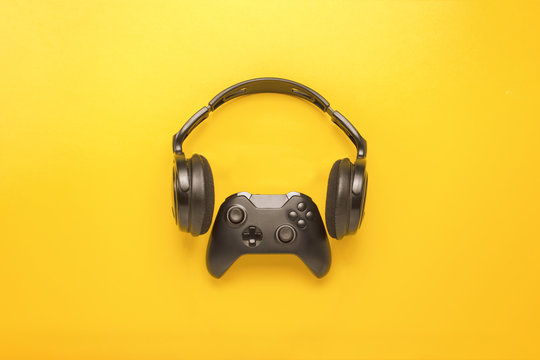 Black headphones and a gamepad on yellow background. Concept of the game on the console or computer. Rest after work. Cybersport. Flat lay, top view