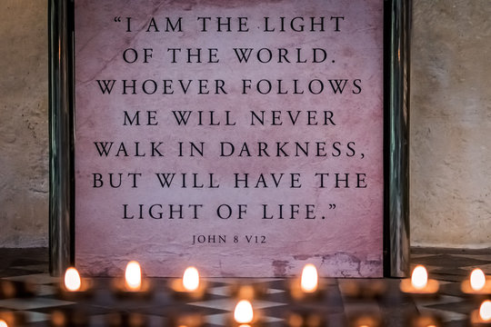 Memorial candles burning in front of a wall plaque with bible verse