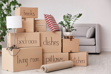 Pile of moving boxes and household stuff in living room