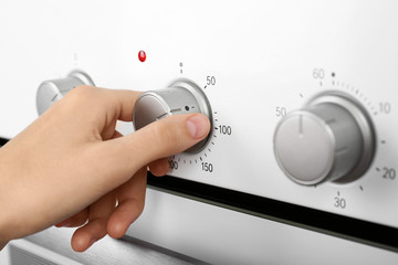 Woman adjusting electric oven, closeup. Kitchen appliance