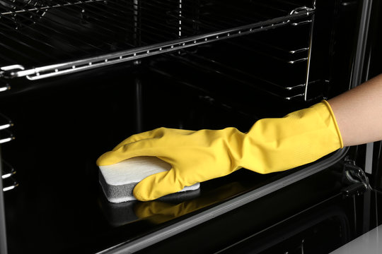 Woman cleaning electric oven with sponge, closeup