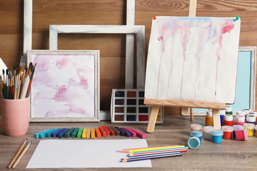 Abstract paintings and set of professional art supplies on table against wooden background