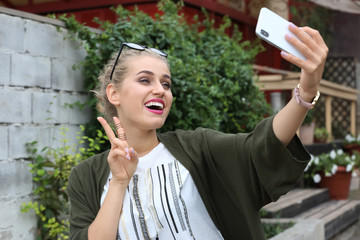 Attractive woman taking selfie on city street