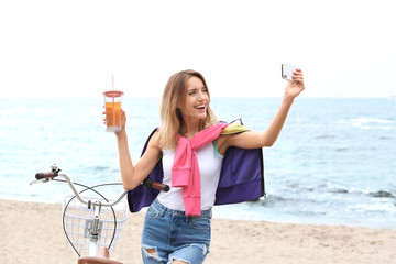 Attractive woman taking selfie near bicycle on sea coast