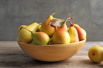 Bowl with ripe pears on table against grey background