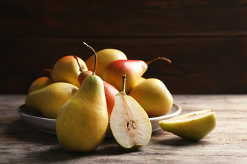 Ripe pears on wooden table against dark background