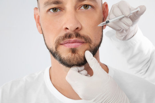 Man getting facial injection on white background, closeup. Cosmetic surgery concept