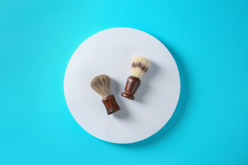 Flat lay composition with shaving brushes on color background