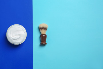 Flat lay composition with shaving brush and cream on color background. Space for text