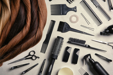 Flat lay composition with different locks of hair and tools on color background