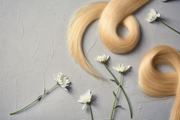 Composition with locks of blond hair and flowers on color background, flat lay