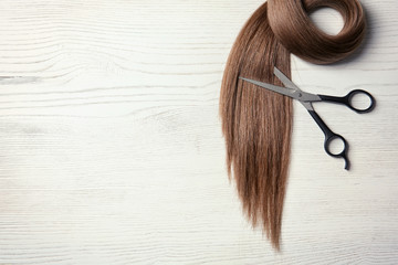 Composition with lock of brown hair on wooden background, top view. Space for text