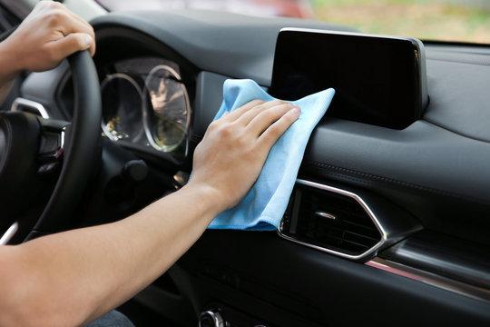 Man washing car salon with rag, closeup