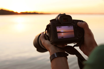 Male photographer holding professional camera with photo of riverside sunset on display