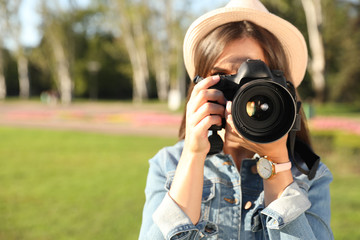 Young female photographer taking photo with professional camera on street. Space for text