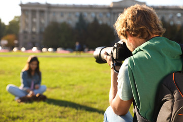 Male photographer taking photo of young woman with professional camera on grass outdoors