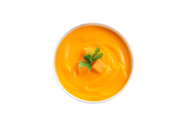 Delicious pumpkin cream soup in bowl on white background, top view