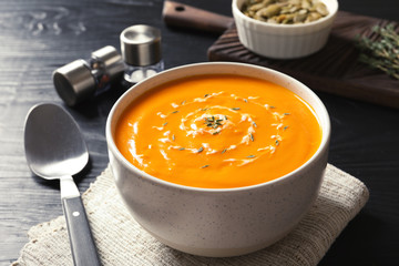 Delicious pumpkin cream soup in bowl on table