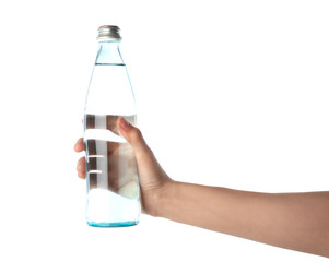 Woman holding glass bottle with water on white background