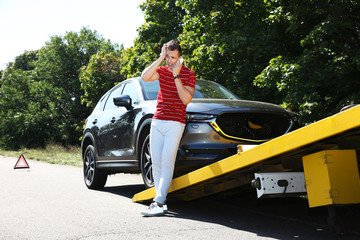 Man talking on phone near broken car and tow truck outdoors