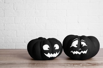 Pumpkins with scary faces near brick wall, space for text. Halloween decor