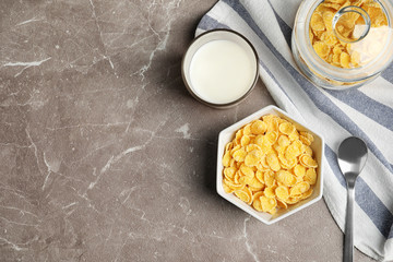 Flat lay composition with healthy cornflakes in bowl on table. Space for text