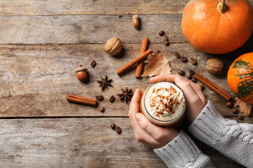 Woman holding glass of tasty pumpkin spice latte on wooden table, flat lay with space for text