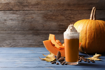 Glass with tasty pumpkin spice latte on wooden table. Space for text