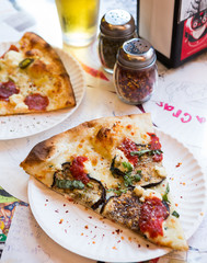 Eggplant pizza with chili flakes on a paper plate.