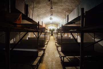 Wooden double-decker beds inside old abandoned soviet bomb shelter