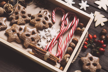 Festive food, family celebration, Christmas and New Year traditions concept. Gingerbread cookies, nuts, cinnamon, anise, decorative snowflakes and candy canes on wooden tray