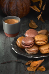 Autumn macarons with caramel and cocoa with coffee on dark rustic wood