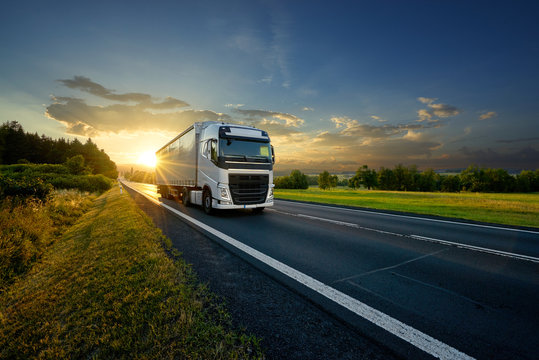White truck driving on the asphalt road in rural landscape in the rays of the sunset