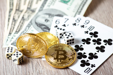 Bitcoins, cards, dices on wooden background. Cryptocurrencie gambling concept
