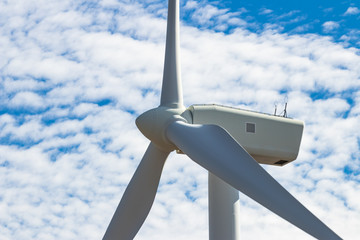 Green sustainable energy windmill power turbine electricity generators on rolling hills with clouds and blue sky