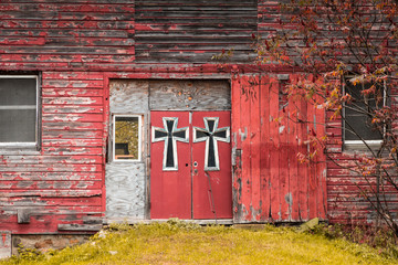 Red barn double doors are adorned in large gothic-style crosses surrounded by fall foliage